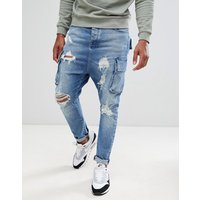 ASOS DESIGN drop crotch jeans in mid wash blue with cargo pockets and rips - Mid wash blue