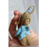 Little Peter loves hopping, in his soft blue coat with its bouncy bunny tail and his hat with flopsy rabit ears, he is a perfect spring gift - Bouncy Gifts