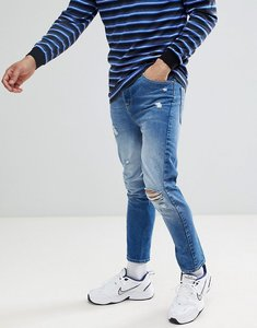 Read more about Asos design twisted skinny jeans in mid wash blue with rips - mid wash blue