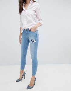 Read more about Asos whitby low rise skinny jeans in mid wash blue with rip and repair - mid wash blue