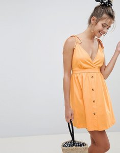 Read more about Asos design mini tie strap button through sundress - apricot