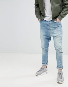 Read more about Asos design drop crotch jeans in mid wash blue with rips - mid wash blue