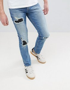 Read more about Asos skinny jeans in mid wash blue with rip repair - mid wash blue