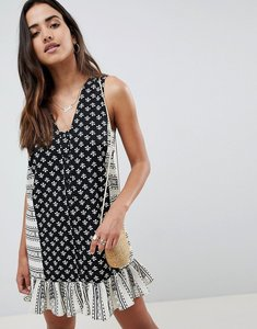 Read more about Asos design tab side button through pep hem mini sundress in mixed print - multi