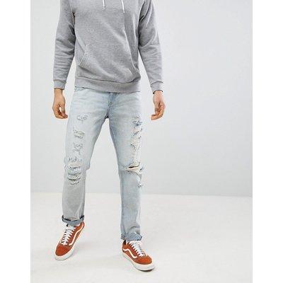 Jeans im Sale - ASOS DESIGN - Schmale Jeans in hellblauer Waschung mit starken Rissen - Blau