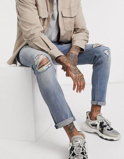 Jeans Blu uomo Jeans skinny lavaggio medio strappati con fondo grezzo - ASOS DESIGN - Blu