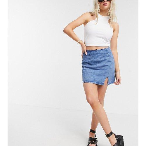 ASOS DESIGN Petite - Mini-jupe en jean fendue sur le côté à délavage moyen - ASOS Petite - Modalova